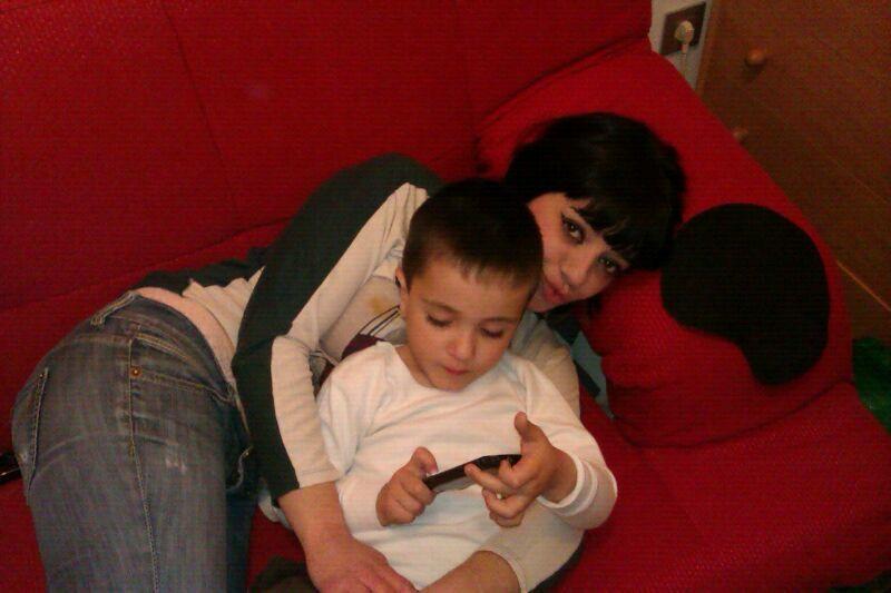 Aitor jugando con el móvil en su casa junto a su madre, Begoña.